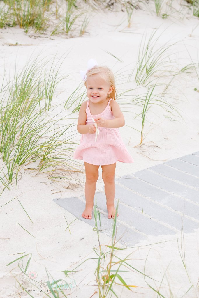 Toddler girl holding a starfish and standing on the boardwalk on the side at Johnsons Beach in Perdido Key Florida