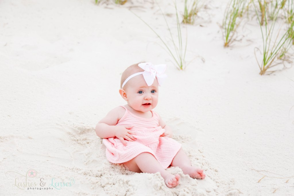 Baby girl sitting in the sand with a big bow around her head at Johnsons Beach in Perdido Key Florida