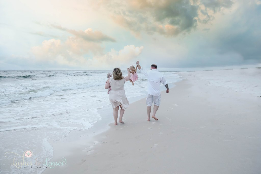 Mom and Dad swinging their toddler daughter and walking along the waters edge with mom holding baby on her hip at Johnsons Beach in Perdido Key Florida