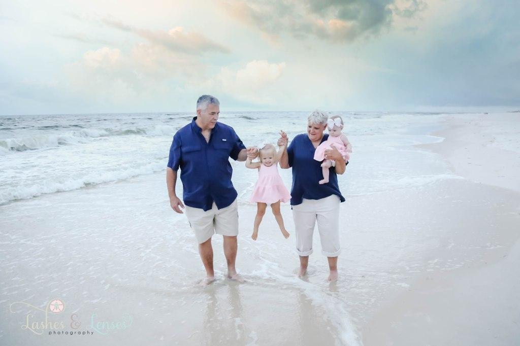 Grandma and Grandpa holding toddler granddaughter with grandma holding baby granddaughter at Johnsons Beach in Perdido Key Florida
