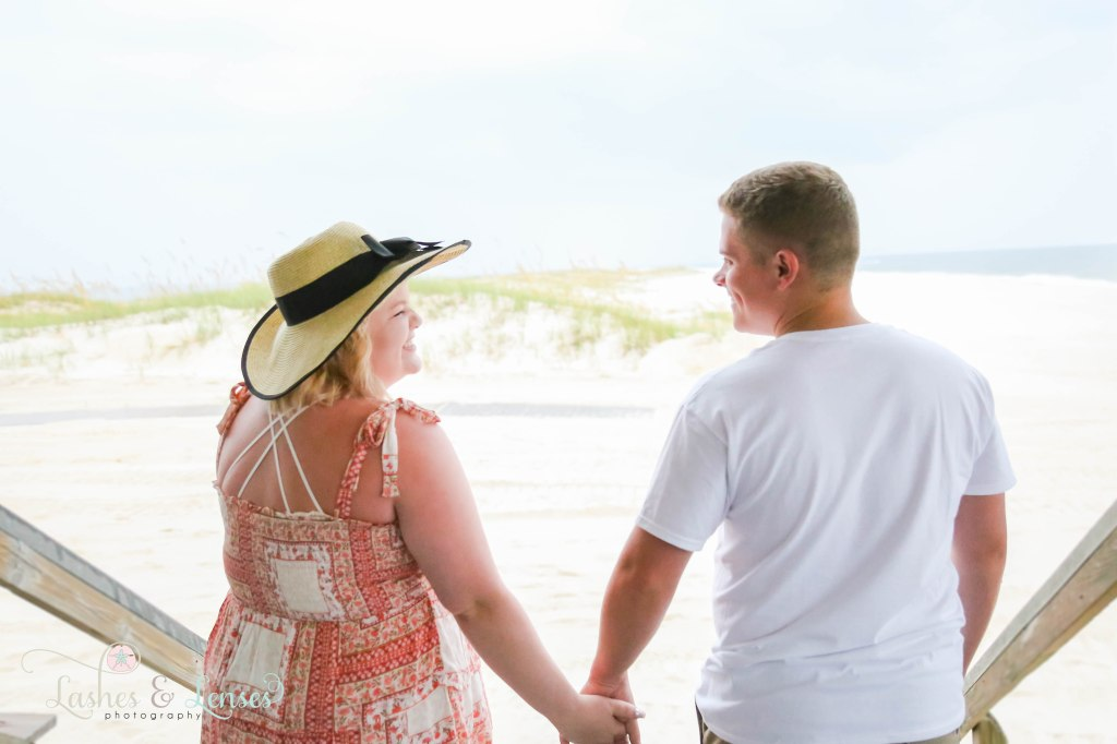 Close up photo of young couple with their back to the camera smiling and laughing with each other at Johnsons Beach in Perdido Key Florida