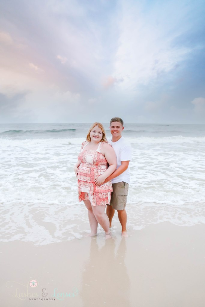 Young married couple standing at the edge of the water with the waves just barely touching them at Johnsons Beach in Perdido Key Florida