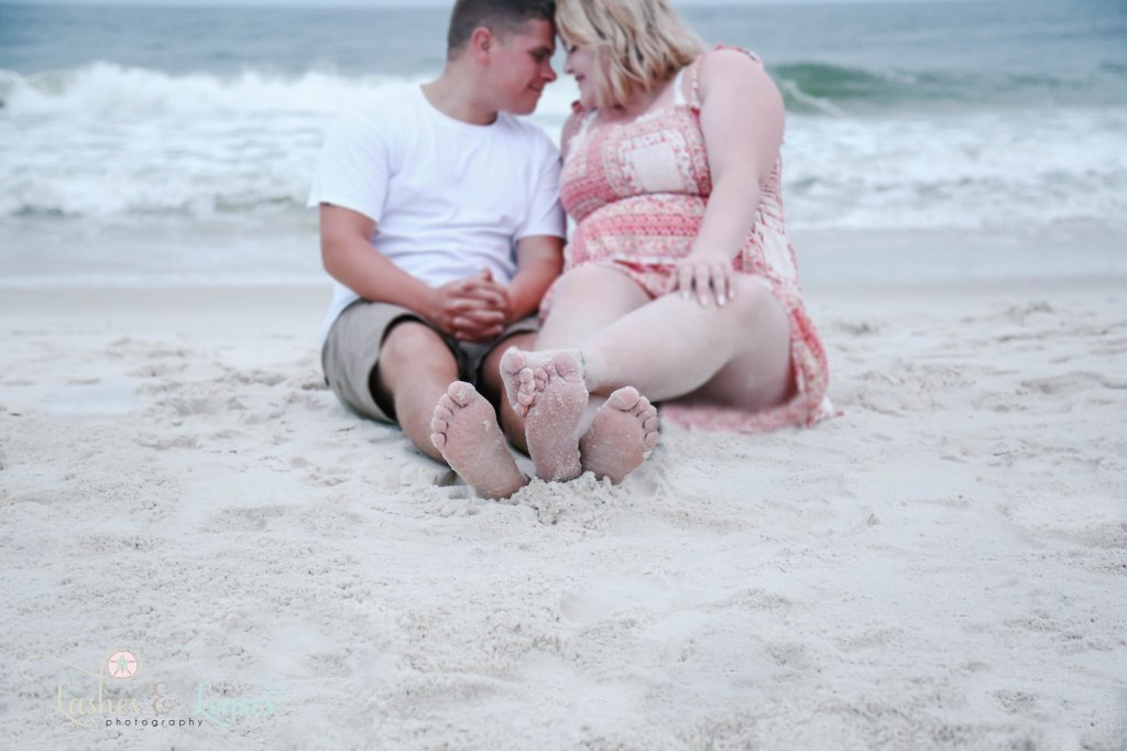 A couple sitting in the sand with the waves crashing behind them, they are out of focus with their feet in focus at Johnsons Beach in Perdido Key Florida