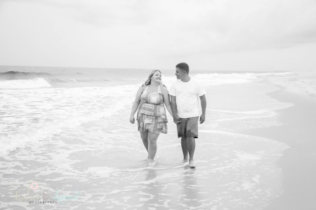 Black and white photo of couple walking hand in hand along the waters edge at Johnsons Beach in Perdido Key Florida