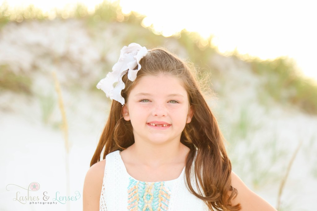 Close up photo of little girl who is missing her front teeth at Johnsons Beach in Perdido Key Florida