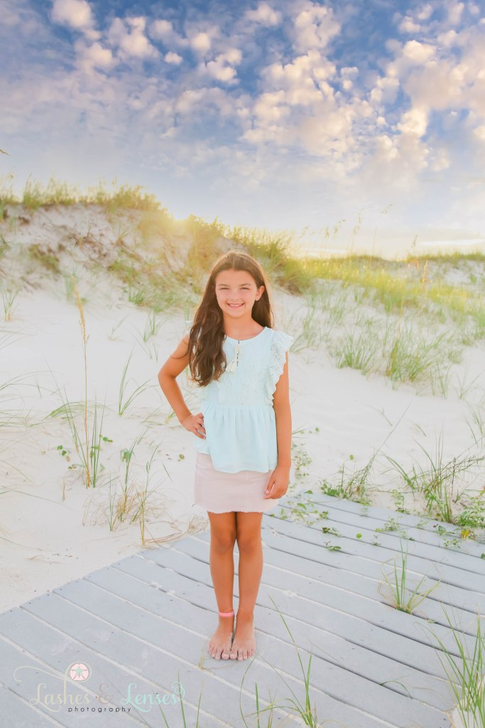 Older girl standing on a washed up boardwalk with the golden sea oats behind her at Johnsons Beach in Perdido Key Florida