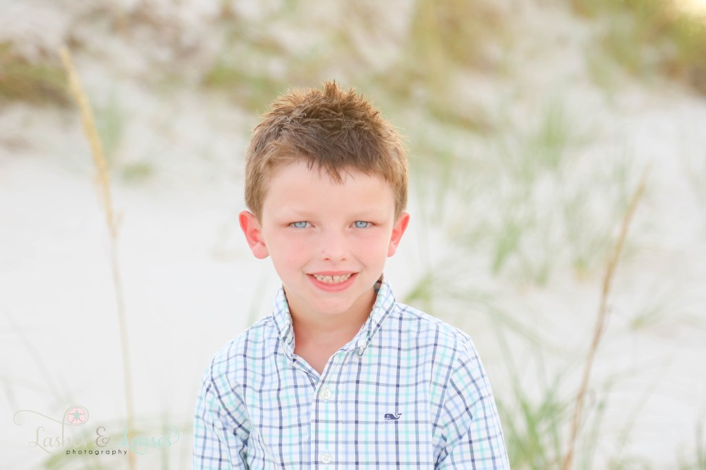 Close up photo of little bout with spiky hair and blue eyes at Johnsons Beach in Perdido Key Florida