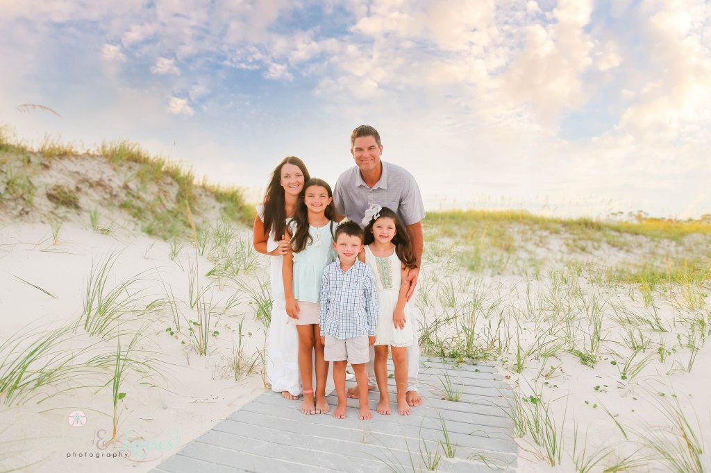Mom and Dad hugging their three children close and standing on a washed up boardwalk at Johnsons Beach in Perdido Key Florida