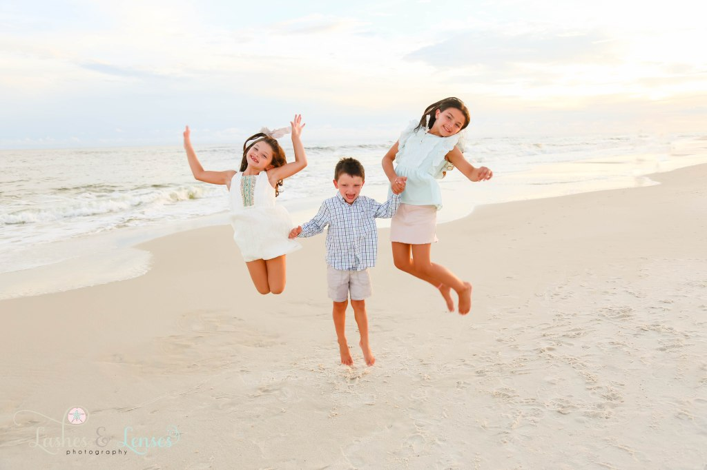 Two sisters and brother jumping for joy at the waters edge at Johnsons Beach in Perdido Key Florida