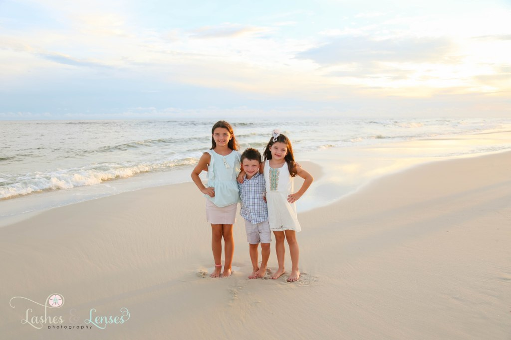 Brother and sisters standing by the waters edge at Johnsons Beach in Perdido Key Florida
