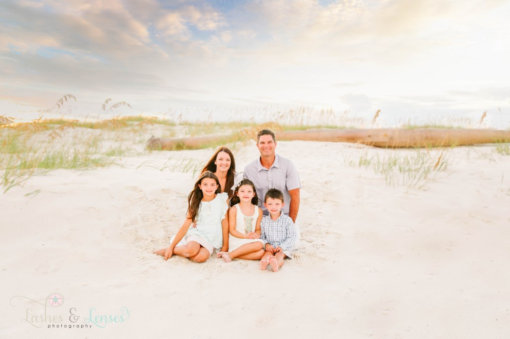Mom, Dad and two daughters and son sitting in the sand with sea oats and a washed up palm tree behind them at Johnsons Beach in Perdido Key Florida