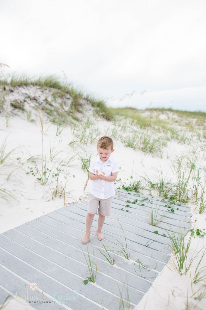 Toddler boy holding and looking down at a starfish in his hands and standing on a washed up boardwalk at Johnsons Beach in Perdido Key Florida