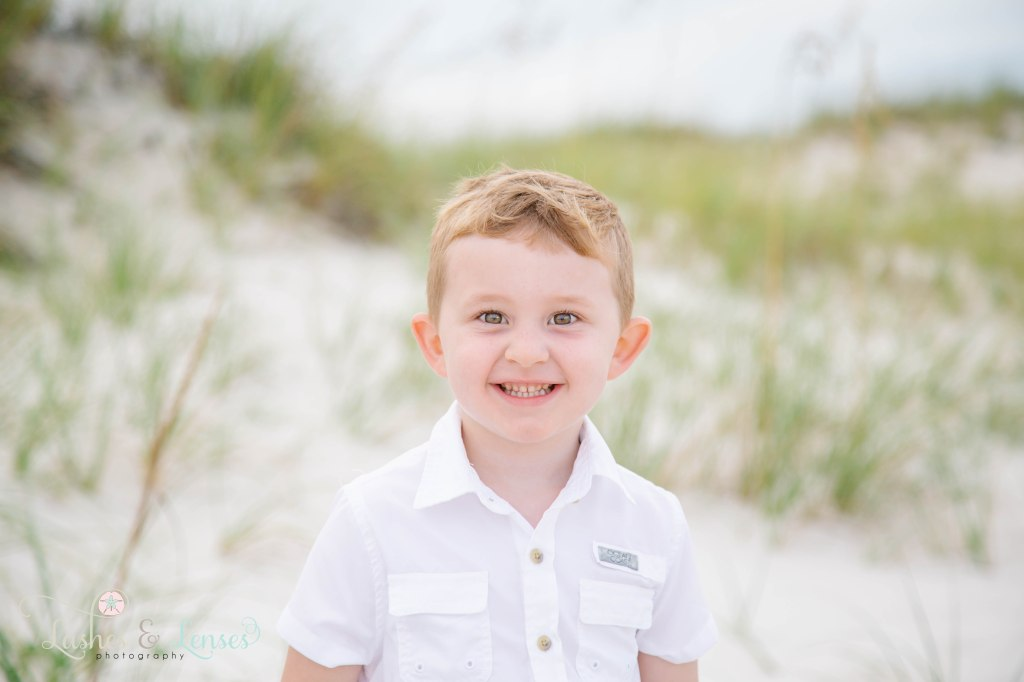 Close up photo of hazel eyed little boy with sand dunes and sea oats behind him at Johnsons Beach in Perdido Key Florida
