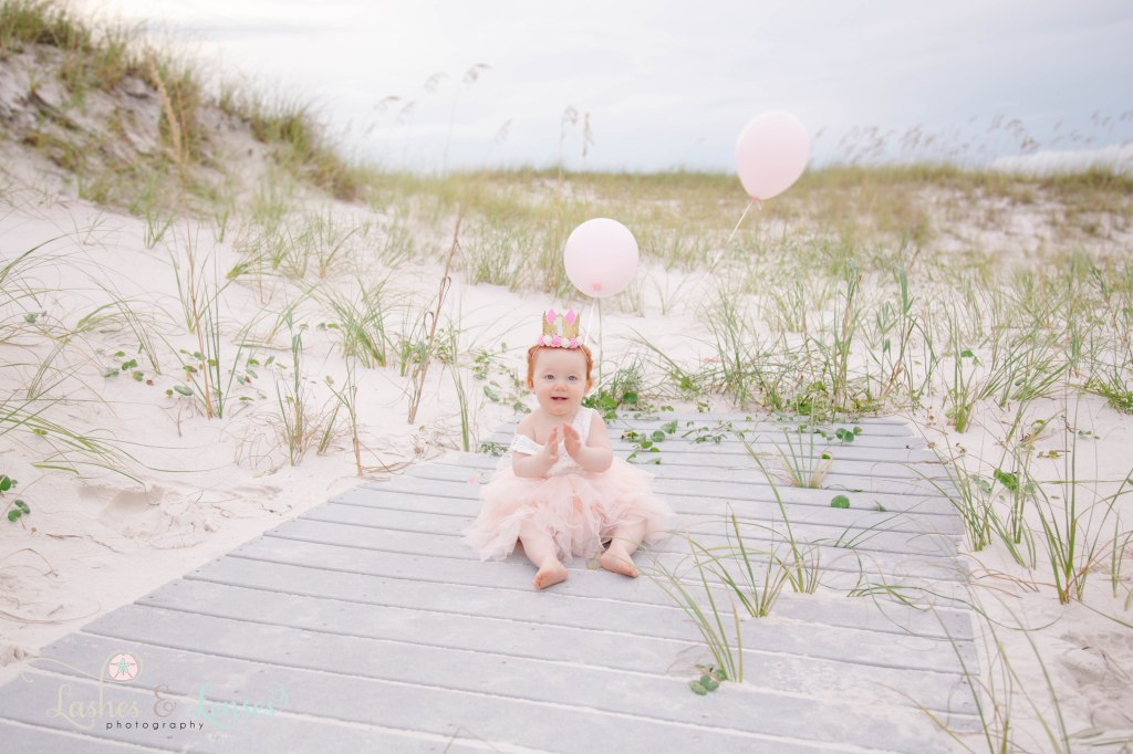 One year old little redheaded girl with a birthday crown on her head and pink balloons behind her, sitting on the boardwalk at Johnson's Beach in Perdido Key, Florida