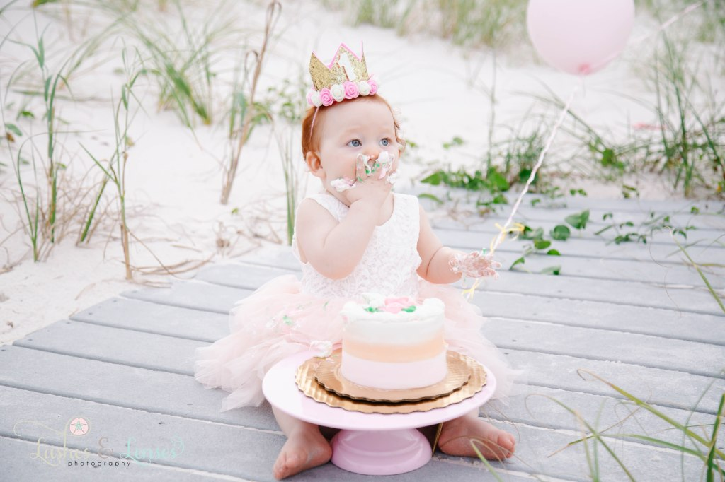 One year old little redheaded girl with a birthday crown on her head doing a cake smash, sitting on the boardwalk at Johnson's Beach in Perdido Key, Florida