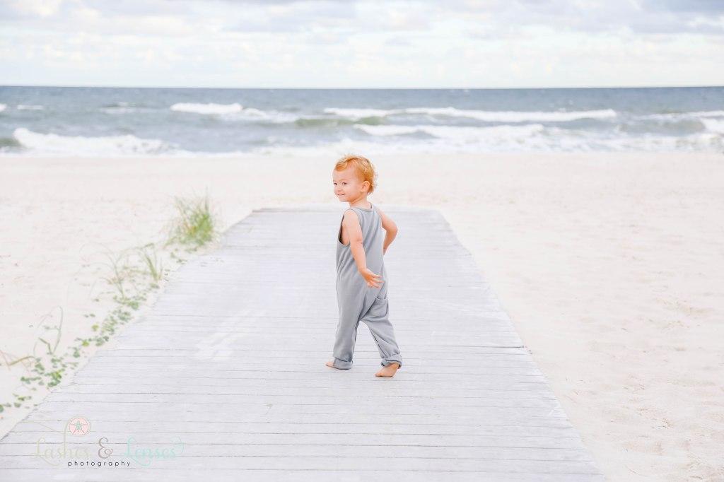 Little boy walking on boardwalk and looking back toward camera at Johnson's Beach in Perdido Key, Florida