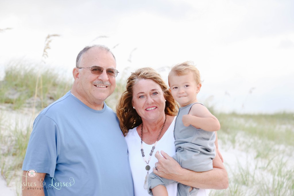 Close up photo of Grandparents holding grandson and looking at the camera at Johnson's Beach in Perdido Key, Florida