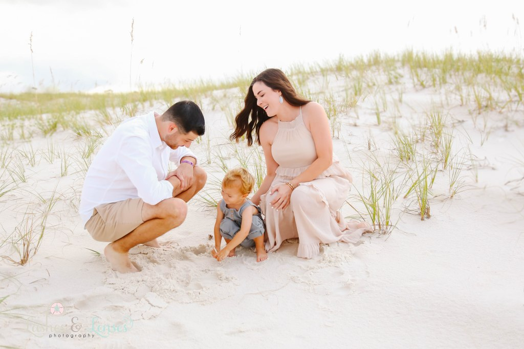 Mom and Dad sitting in the sand and looking at their son playing in the sand at Johnson's Beach in Perdido Key, Florida