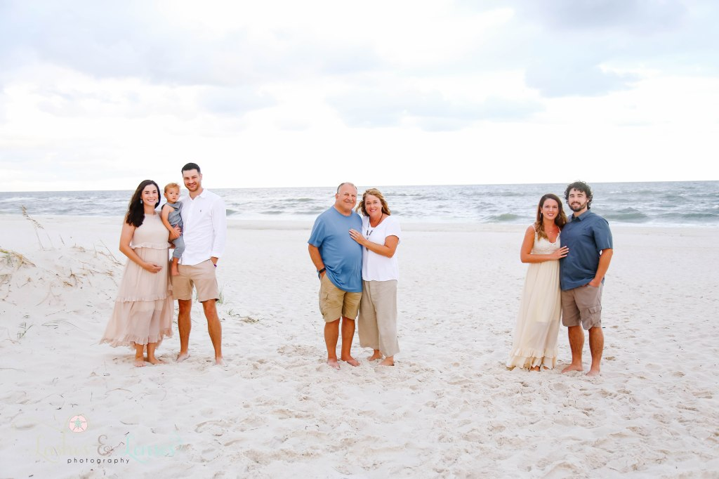 Extended family standing in their family groups with the water behind them at Johnson's Beach in Perdido Key, Florida