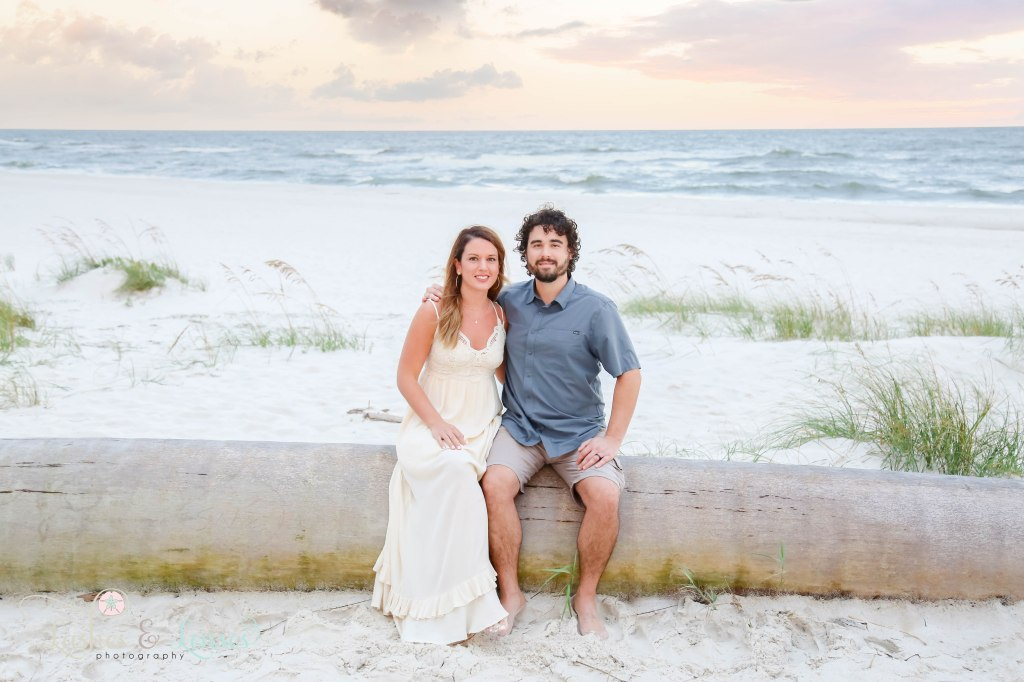 Husband and wife sitting on a washed up palm tree with a colorful sunset behind them at Johnson's Beach in Perdido Key, Florida