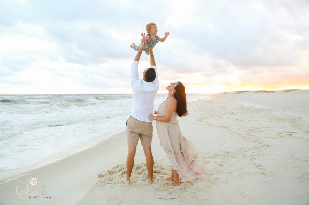 Dad throwing son in the air with mom looking up at their son, they are standing next to the water at Johnson's Beach in Perdido Key, Florida