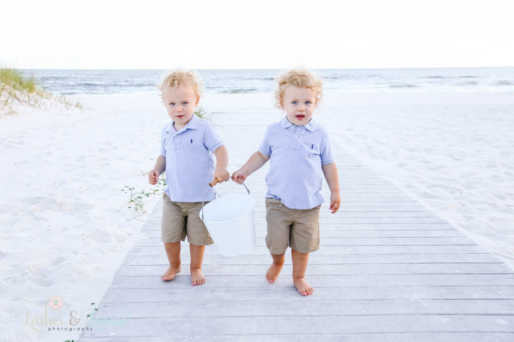 Twin two year old boys walking on boardwalk towards the camera with the water behind them at Johnson's Beach in Perdido Key, Florida