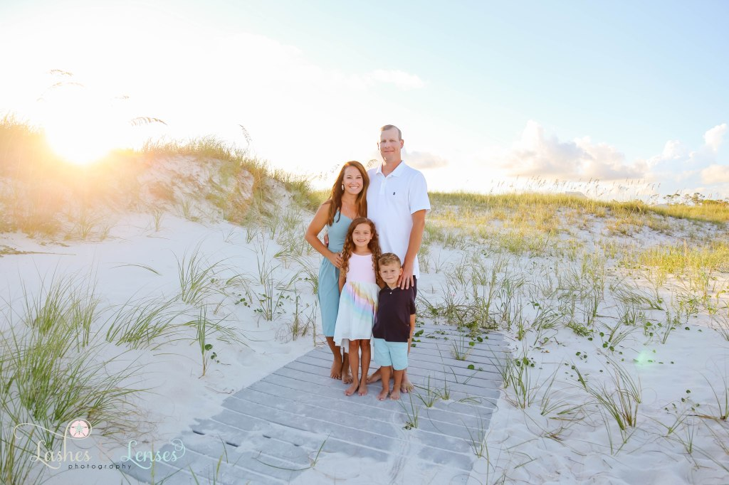Mom, Dad and son and daughter standing on a washed up boardwalk with the sand dunes behind them at Johnson's Beach in Perdido Key, Florida