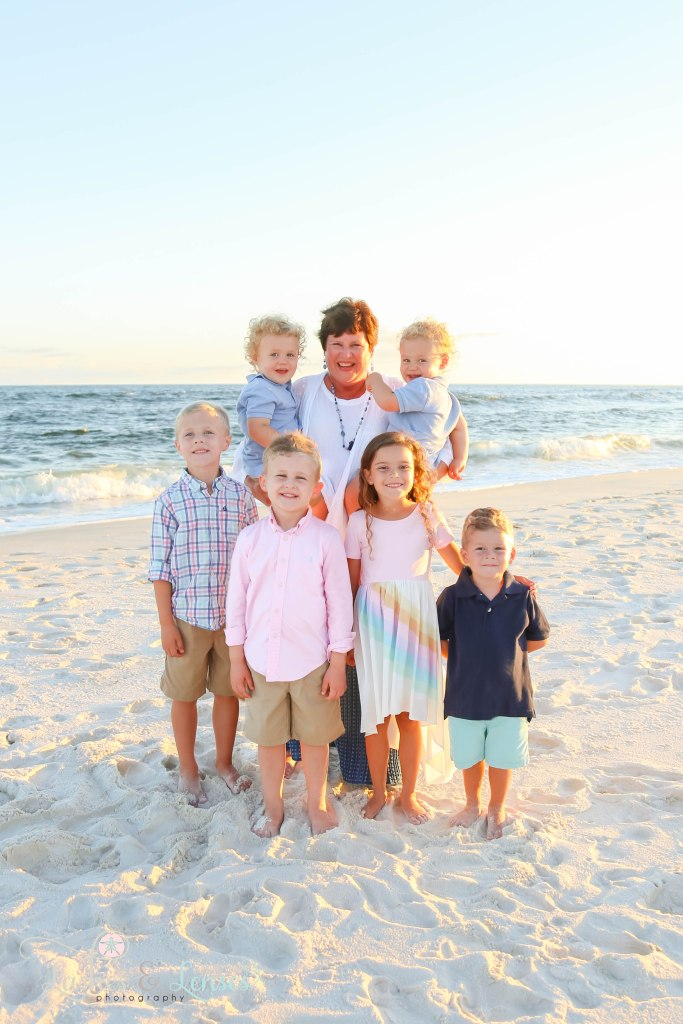 Grandma with her six small grand children standing by the edge of the water at Johnson's Beach in Perdido Key, Florida