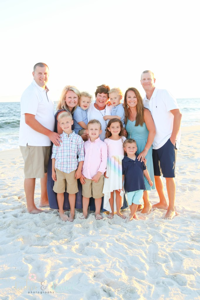 Large extended family all huddling close with the water behind them at Johnson's Beach in Perdido Key, Florida