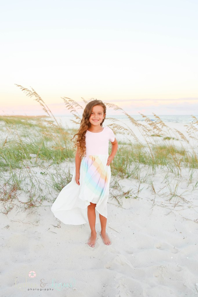 Young girl standing in the sand with the water, sea oats and sand dunes behind her at Johnson's Beach in Perdido Key, Florida