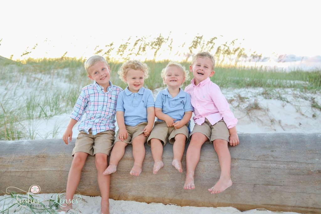 Four young brothers sitting on a washed up palm tree with the sunset and golden sea oats behind them at Johnson's Beach in Perdido Key, Florida