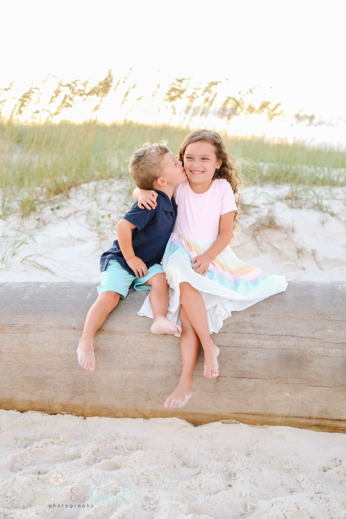 Little brother giving big sissy and sloppy kiss on the cheek, they are sitting on a washed up palm tree at Johnson's Beach in Perdido Key, Florida