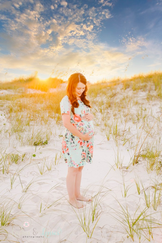 Pregnant woman holding her belly with the sunset behind her as well as sea oats and sand dunes at Johnson's Beach in Perdido Key Florida