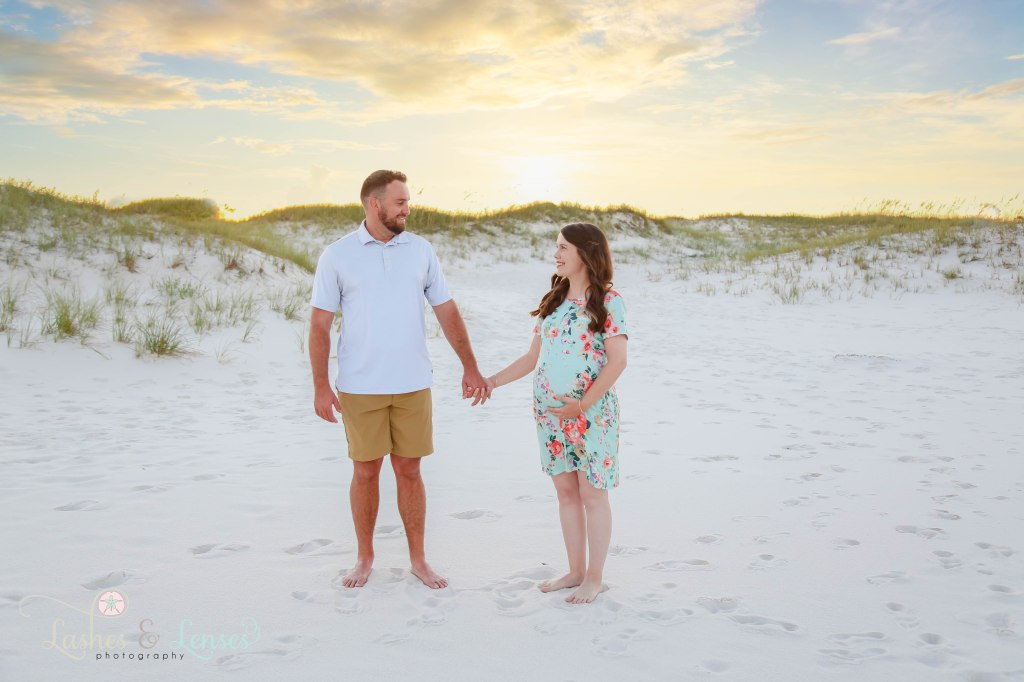 Husband and wife holding hands and getting ready to walk with the large sand dunes behind them at Johnson's Beach in Perdido Key Florida