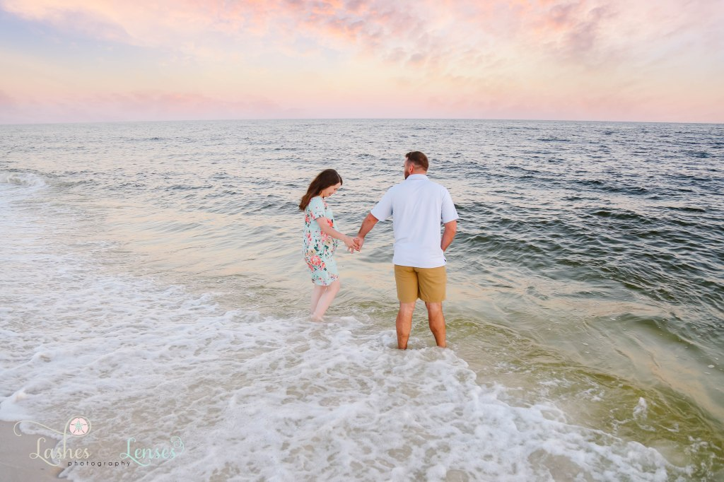 Pregnant wife and her husband walking in the waves at Johnson's Beach in Perdido Key Florida
