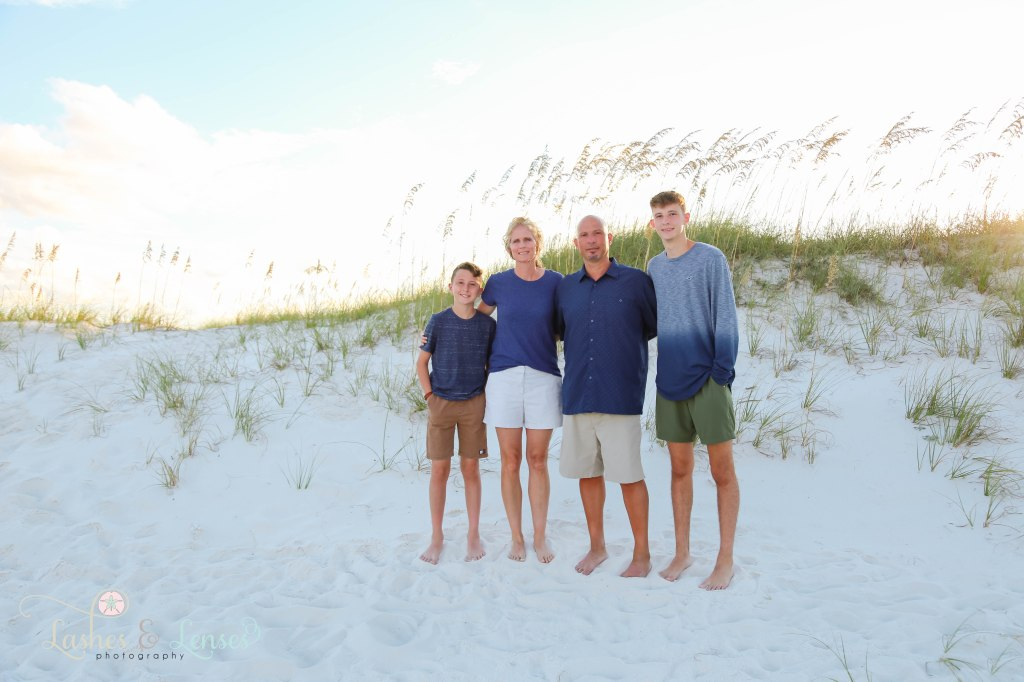 Family of four standing in front of the sand dunes with the golden sea oats behind them at Johnsons Beach in Perdido Key Florida