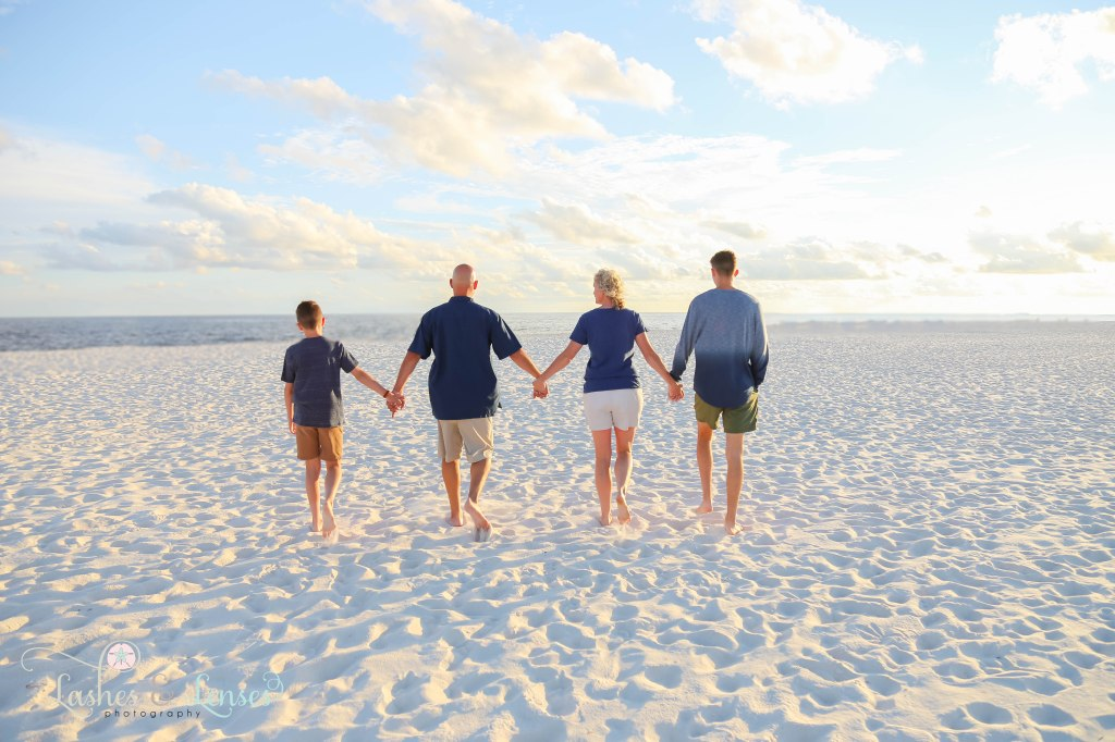Family of four walking hand in hand towards the water with their backs to the camera at Johnsons Beach in Perdido Key Florida