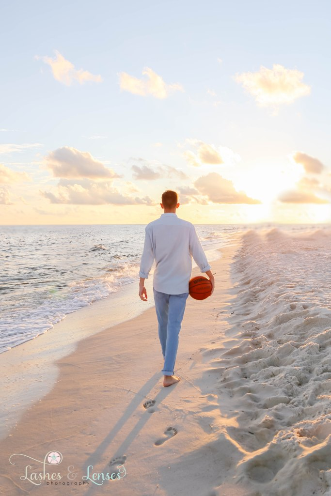 Senior boy holding his basketball and walking down the beach with his back to the camera at Johnsons Beach in Perdido Key Florida