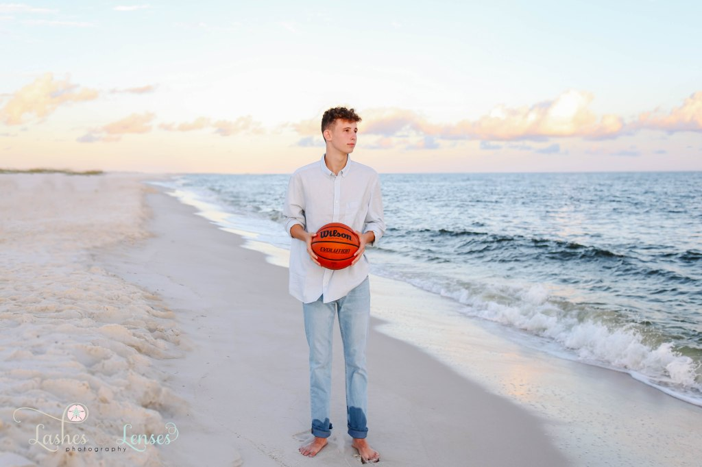 Senior boy holding his prized basketball and standing on the beach and looking away from the camera at Johnsons Beach in Perdido Key Florida