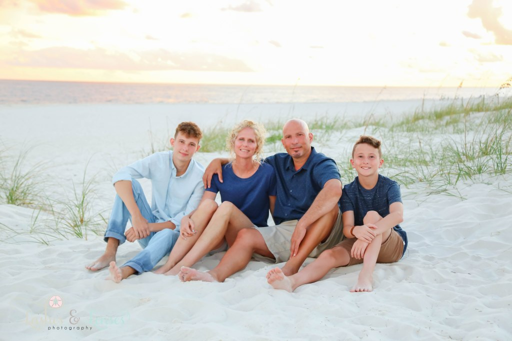 Mom, Dad and their two sons sitting in the sand with the water behind them at Johnsons Beach in Perdido Key Florida