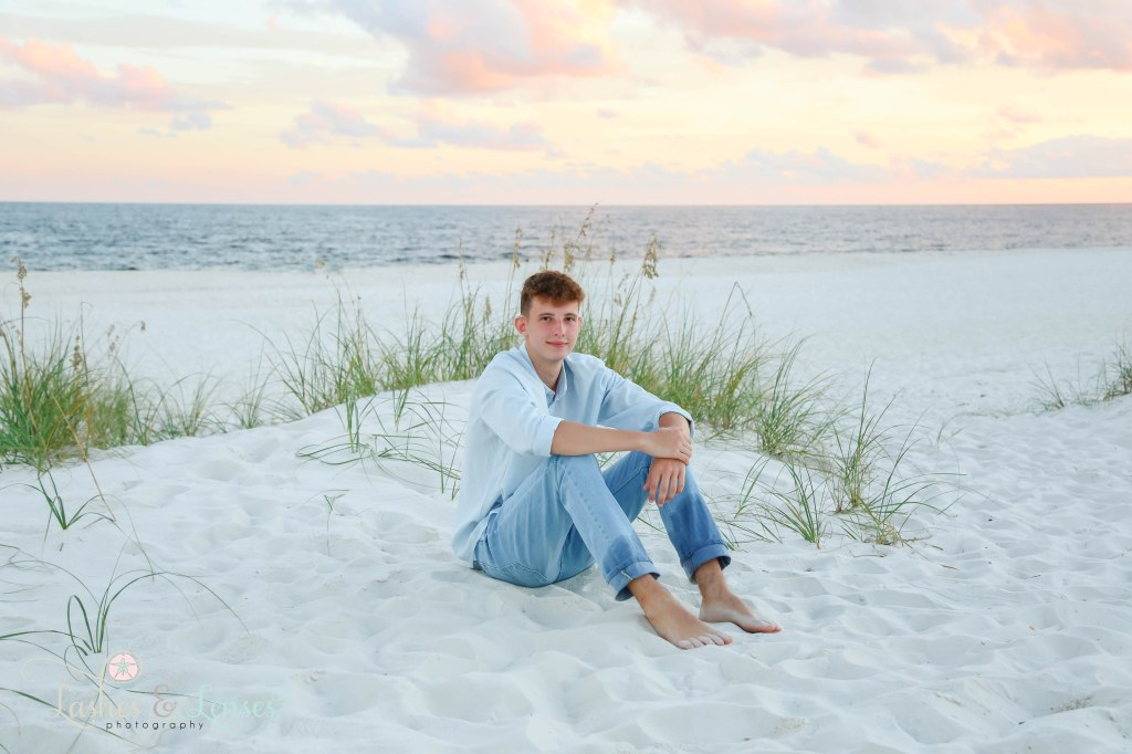 Senior boy sitting in the sand with a small sand dune behind him as well as the water at Johnsons Beach in Perdido Key Florida