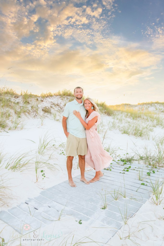 Husband and Wife standing on a washed up boardwalk with the sunset behind them at Johnsons Beach in Perdido Key Florida