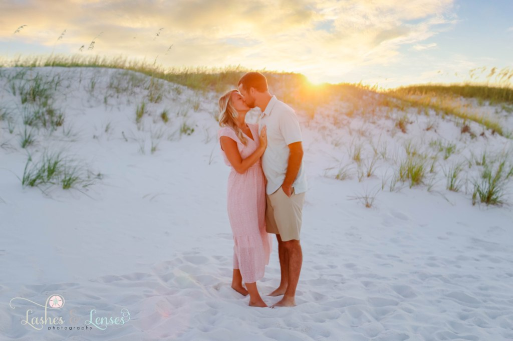 Husband and wife kissing with the sunset behind them at Johnsons Beach in Perdido Key Florida