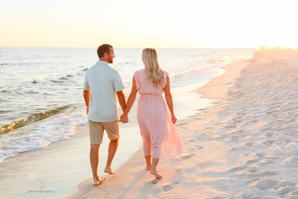 Husband and wife walking along the waters edge towards the sunset at Johnsons Beach in Perdido Key Florida