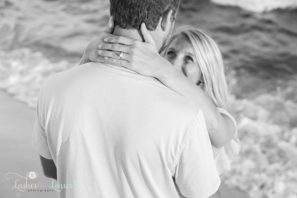 Black and White photo of wife hugging her husband and pulling him in for a kiss at Johnsons Beach in Perdido Key Florida