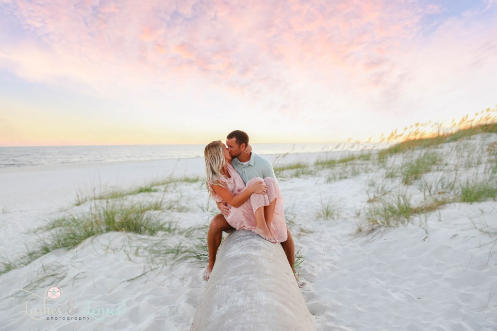 Wife and Husband sitting on a washed up palm tree with the colorful sunset behind them at Johnsons Beach in Perdido Key Florida