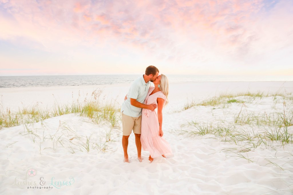 Husband and wife kissing with the water and sand dunes behind them at Johnsons Beach in Perdido Key Florida