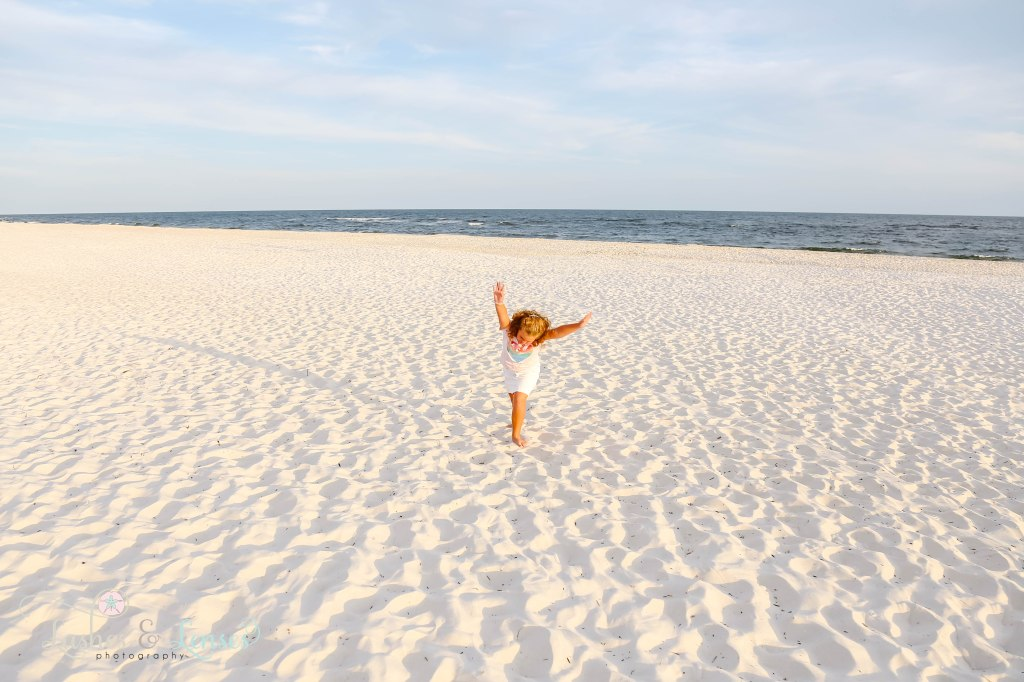 Little girl doing a headstand in the sand at Johnsons Beach in Perdido Key Florida