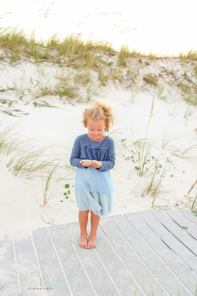 Little girl holding a starfish in her hands and standing on the boardwalk with the sand dunes behind her at Johnsons Beach in Perdido Key Florida