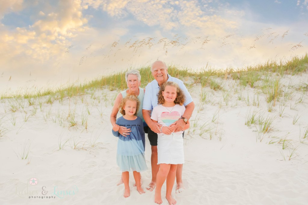 Grandma and Grandpa hugging their two granddaughters with the sand dunes behind them at Johnsons Beach in Perdido Key Florida